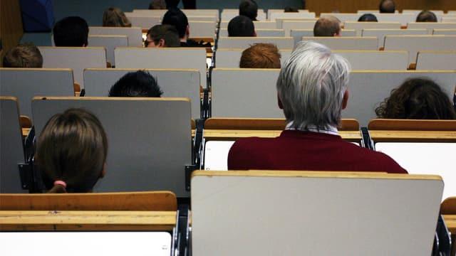 Blick in einen Hörsaal mit gemischtem Publikum jeden Alters.