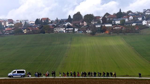 Flüchtlinge laufen hinter Polizeiwagen her, dahinter ein bayrisches Dorf.