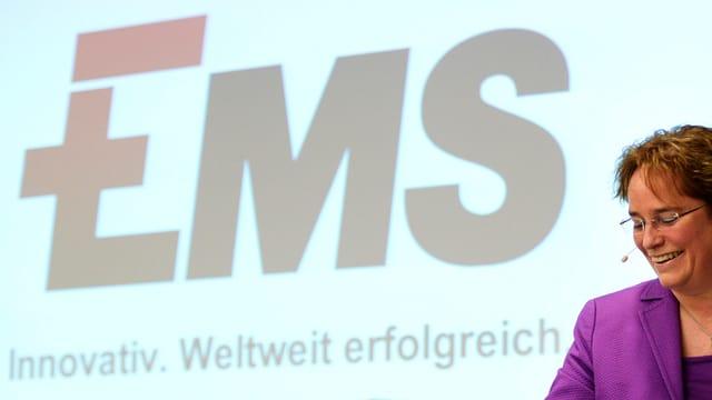 Martullo davant ina projecziun cun logo Ems, ella rì.