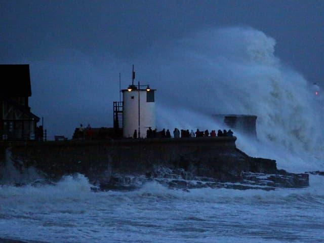 Grosse Welle prallt auf Ufer, Leuchtturm.