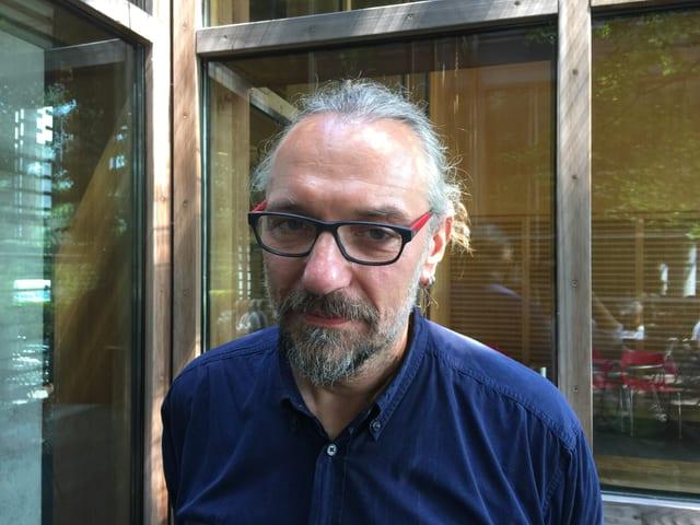 Grauer Bart, markante Brille, Haarzopf