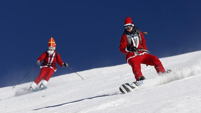 Eine als Samichlaus verkleidete Snowboarderin und ein ebenso verkleideter Skifahrer.