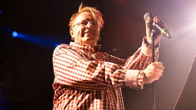 Der Sänger, etwas dicklich, steht lächelnd auf der Bühne.