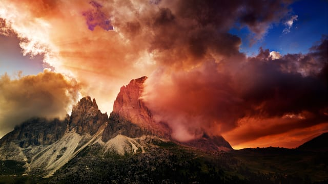 Ein Sturm braut sich über den Berggipfeln zusammen.