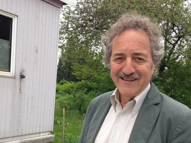 Zu sehen ist ein Mann mit weissem Hemd und grauem Jackett, der in die Kamera blickt und lächelt. Im Hintergrund sind ein Teil einer Barracke und einige grüne Büsche zu sehen.