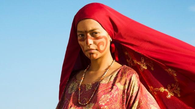 Frau mit wehendem rotem Kopftuch und bemaltem Gesicht