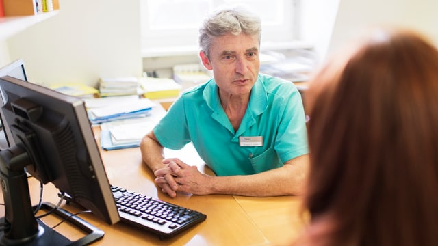 Purtret d'in medi avant in computer, durant discurrer cun pazient.