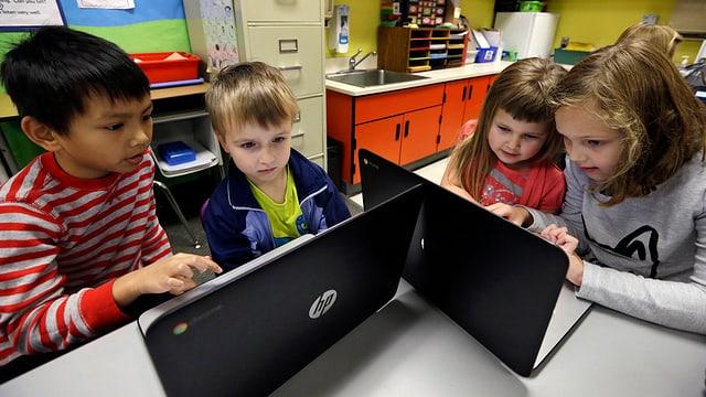 Ein Gruppe von Kindern um zwei Computer.
