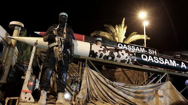 Ein maskierter Mann steht vor zwei Qassam-Raketen in Gaza City