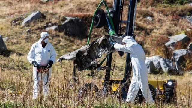 Zwei Unfallermittler in weissen Anzügen bergen einen Teil des Helikopterfahrgestells, das an einem Kran hängt