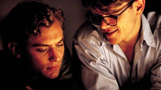 Ein Mann mit Brille lächelt und schaut schräg zu einem anderen Mann.
