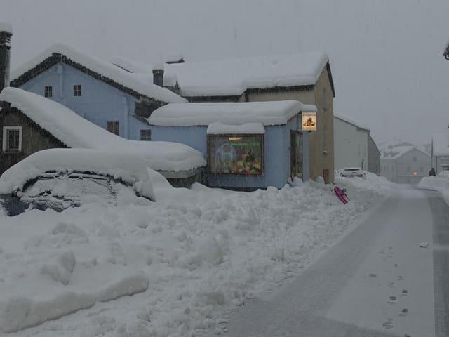 Foto eines Dorfes mit Häusern und viel Neuschnee auf den Dächern und Strassen. Alles ist tief verschneit.
