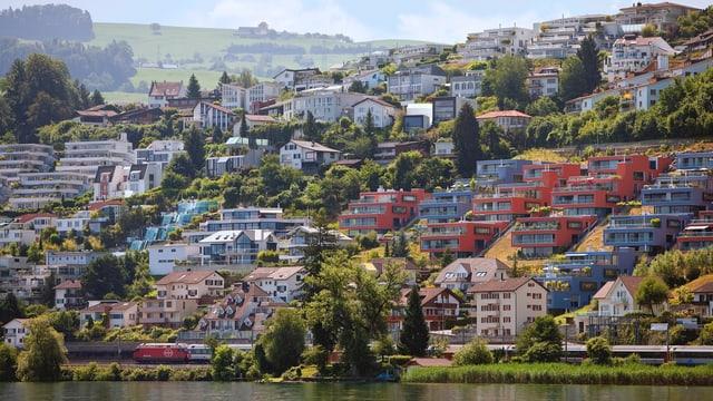 Aufnahme vom See aus in Richtung Bäch, Kanton Schwyz: Luxus-Mehrfamilienhäuser am Hang gebaut, alle mit Aussicht auf den Zürichsee.