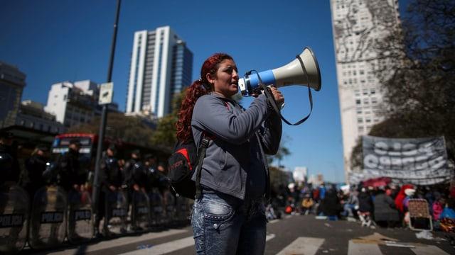 Frau mit Megaphon, dahinter Protestierende Menschen.