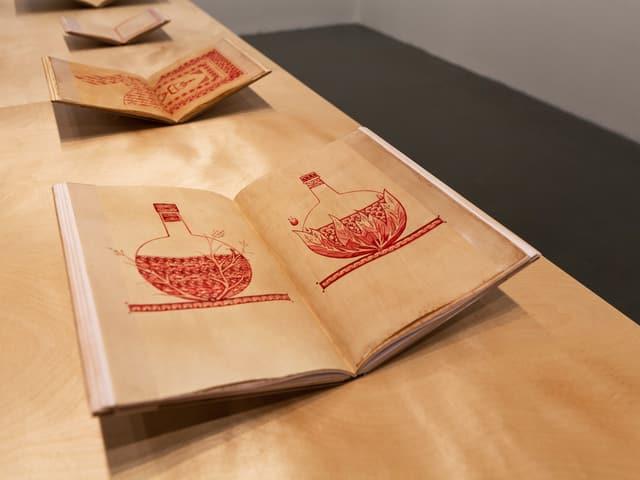 Aufgeschlagene Bücher zeigen filigrane Zeichnungen aus roter Farbe.
