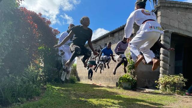 Schüler hüpfen beim Taekwondo-Training hoch in die Luft