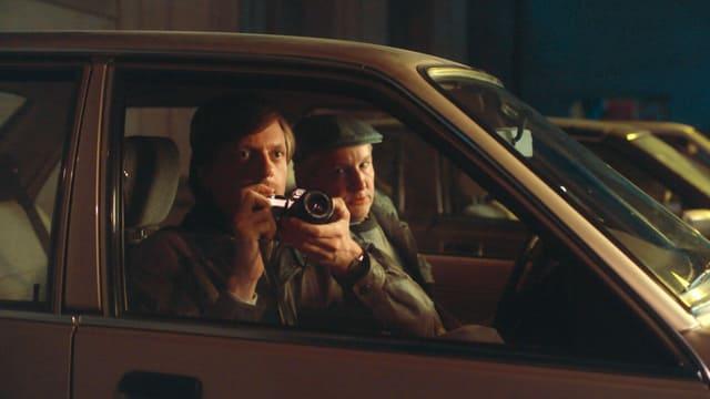 Zwei Männer in einem Auto. Der eine von ihnen hält eine Kamera in der Hand.