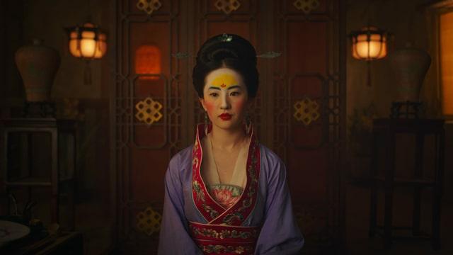 Mulan sitzt geschminkt und traditionell gekleidet an einem Tisch.