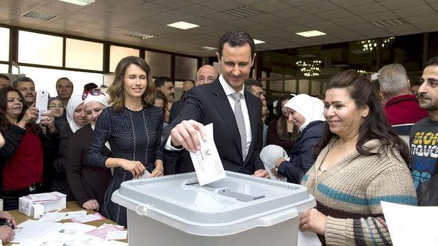 Il maletg mussa co Baschar al-Assad metta il cedel da votar en l'urna.
