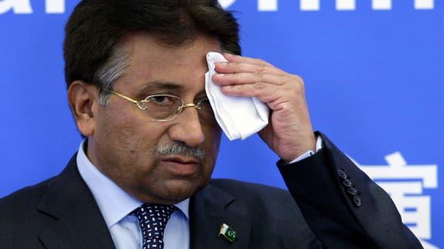 Musharraf tupft sich vor blauem Hintergrund den Schweiss von der Stirn.