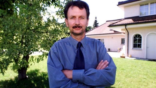 Müller, noch mit Schnauz, posiert vor einer Villa.