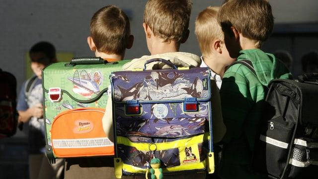 Kinder stehen in einer Gruppe, auf dem Rücken tragen sie Schulrucksäcke.