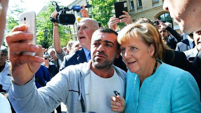 Angela Merkel posiert mit einem Mann vor dessen Smartphone.