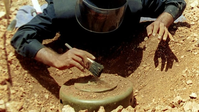 Ein Mitglied der UNO-Friedenstruppen bei der Entschärfung einer Landmine.