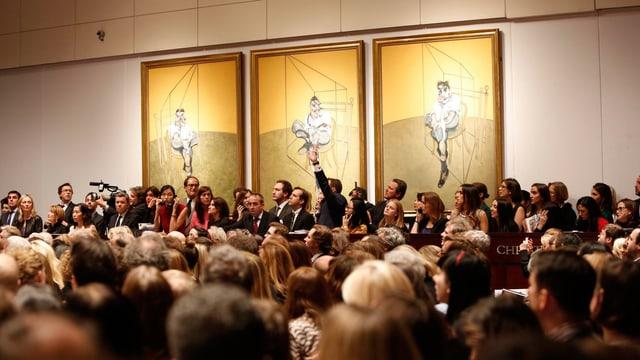 Zahlreiche Menschen sitzen in einem Saal, an dessen Wand drei Kunstwerke hängen.