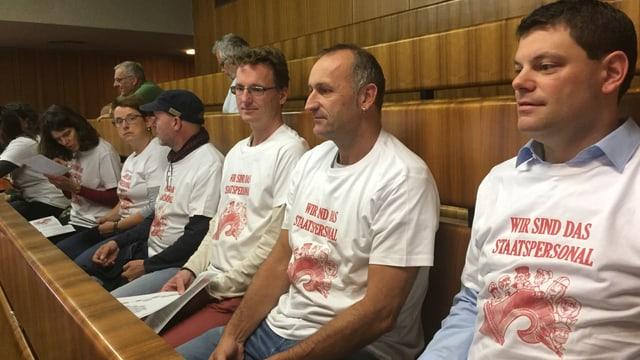 Männer und Frauen sitzen auf der Tribüne, sie tragen ein T-Shirt mit der Aufschrift: Wir sind das Staatspersonal.