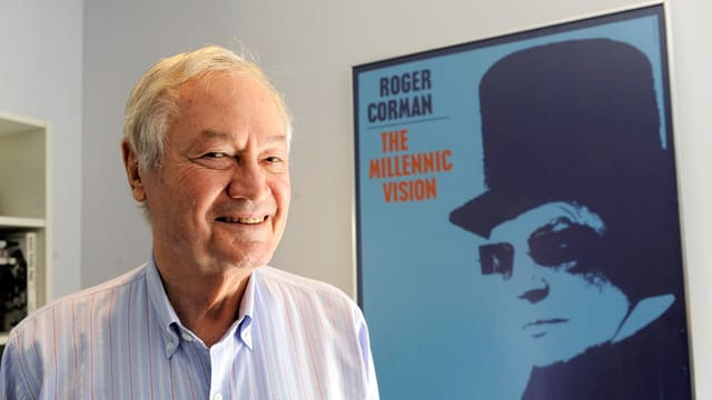 Roger Corman, ein Mann mit grauen Haaren, steht neben einem Filmplakat und lächelt.
