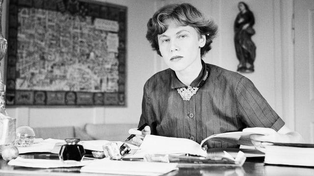 Frau sitzt an einem Schreibtisch mit einem Stift in der Hand. Vor ihr liegen Bücher. Sie schaut in die Kamera. Schwarzweiss Foto.