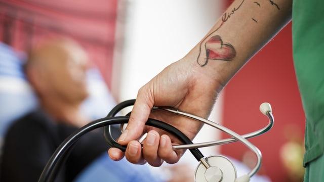 Eine Ärztin mit tätowiertem Arm hält ein Stetoskop in der Hand.
