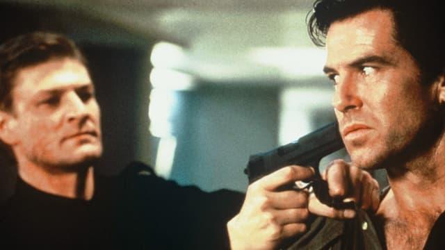 Ein Mann wird von einem anderen Mann mit der Waffe bedroht.
