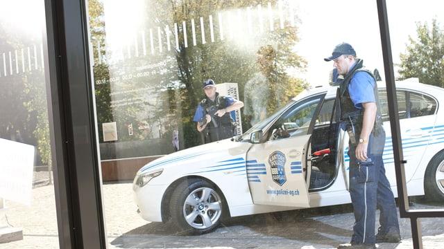Polizisten vor Polizeiauto.