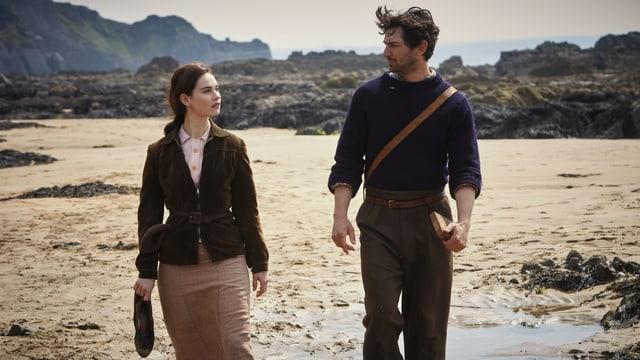 Juliet und Dawsey laufen nebeneinander durch die karge Insellandschaft.
