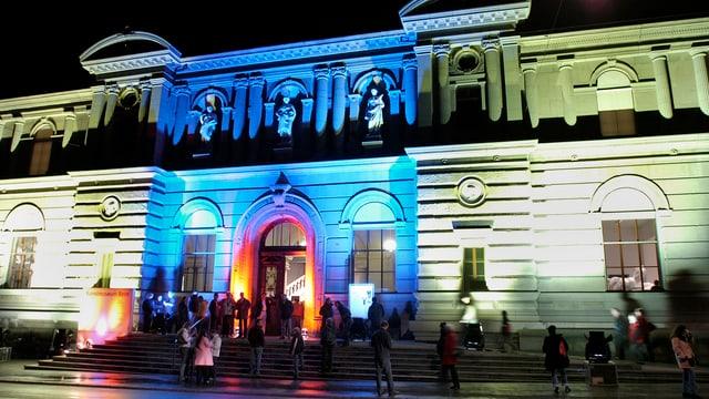Fassade des Museums bei Nacht, blau und grün beleuchtet.