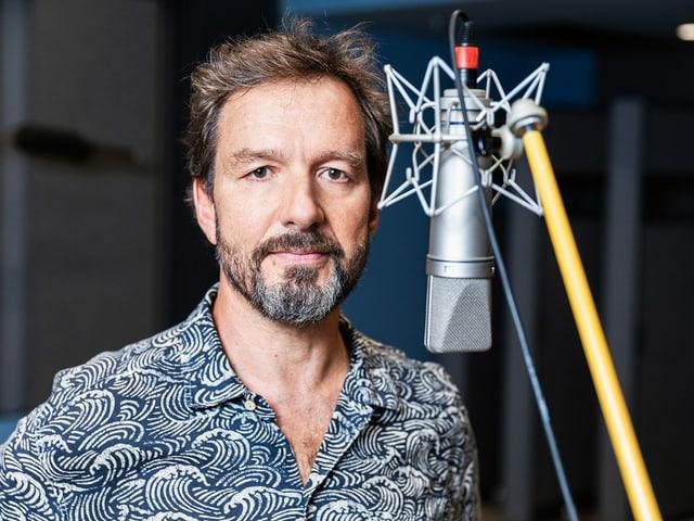 Mann in buntem Hemd vor einem Mikrofon