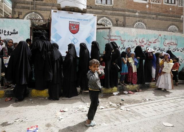 Verschleierte Frauen und Kinder stehen an.