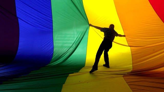 Regenbogenfahne wird von Mann gerafft.