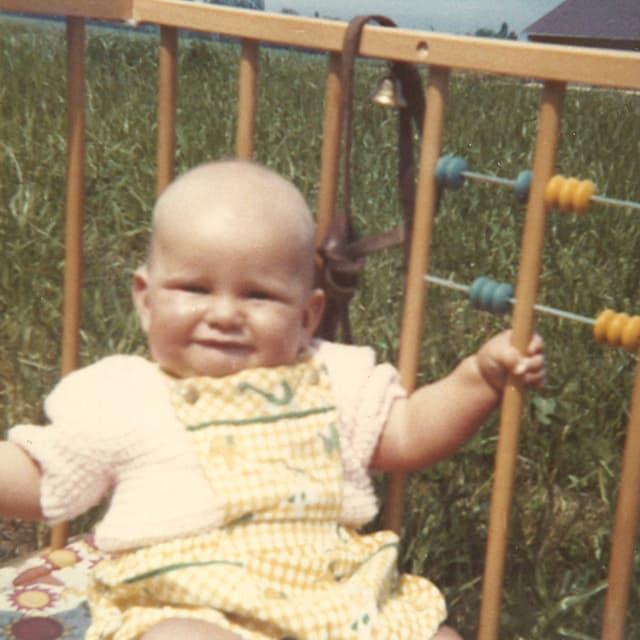Ein Kleinkind sitzt auf einer Wiese in einem Laufgitter.
