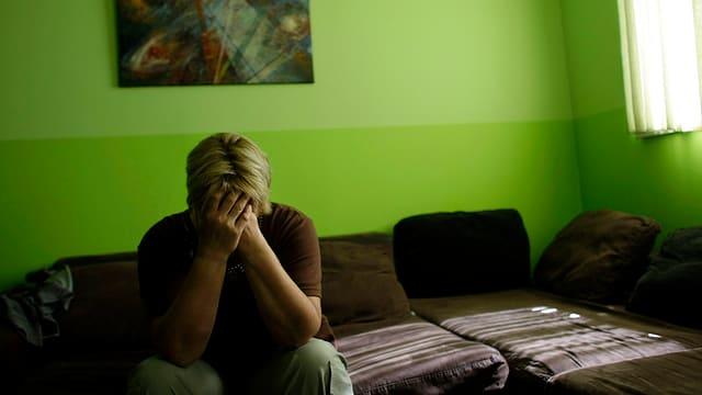 Frau sitzt auf dem Sofa. Die Arme vor das Gesicht geschlagen.