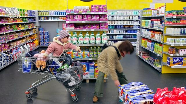 Eine Mutter mit einem Kleinkind im Einkaufswagen beim Einkaufen
