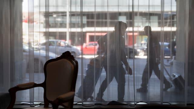 Blick aus einer Hotellobby durch ein Fenster mit Vorhang auf zwei Touristen, die auf dem Trottoir ihre Rollkoffer ziehen.