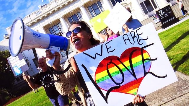 Eine Demonstrantin in Charlottesville mit «We are Love»-Schild.