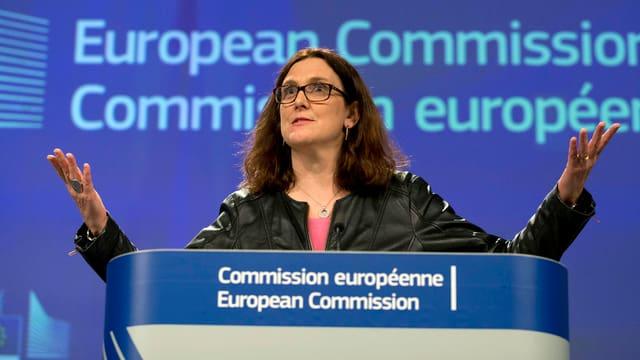 Frau mit Brille und dunklen langen Haaren an Stehpult.