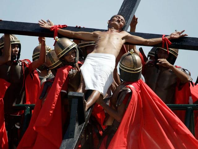 Person am Kreuz mit durchgenagelten Händen.