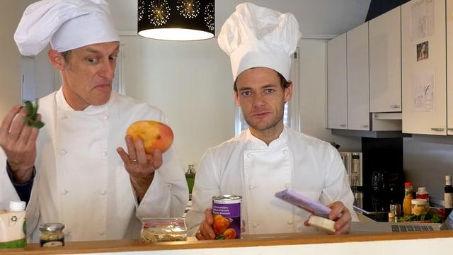 Zwei Männer in Kochkleidung halten Zutaten in die Kamera.
