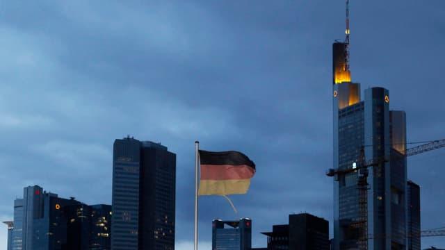 Hochhäuster vor einem dunklen Himmel, eine deutsche Flagge weht im Wind.