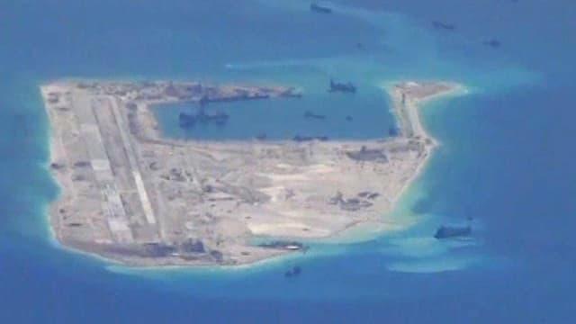 Kleine Insel mit Schiffen, die mit Baggerarbeiten die Landfläche vergrössern.
